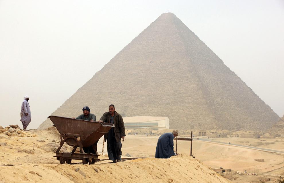 25. Рабочие на месте раскопок перед пирамидами Гиза 11 января 2010 года. Египетские археологи недавно раскопали несколько могил рабочих, строивших крупнейшую пирамиду, датируемую временем правления четвертой династии (2694 – 2513 до н.э.) (VICTORIA HAZOU/AFP/Getty Images)