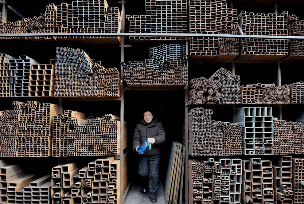 28. Рабочий выходит из магазина на рынке, где продают, стальные изделия, в Шеньяне, провинция Ляонин, 21 января 2010 года. (REUTERS/Sheng Li)