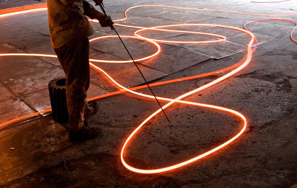 31. Рабочий сталелитейного завода работает с расплавленными прутьями в Исламабаде 20 января 2010 года. (Asad Zaidi/Bloomberg)