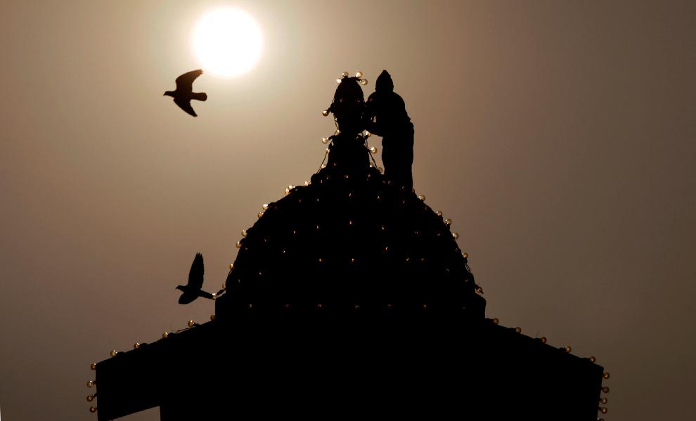 36. Рабочий подсвечивает южный блок здания правительства в преддверии дня Республики в Нью-Дели 22 января 2010 года. (AP Photo/Manish Swarup)