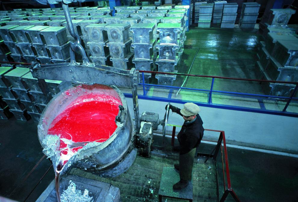 37. Рабочий выливает расплавленный алюминий на Богословском алюминиевом заводе «Русал». (Rusal via Bloomberg)