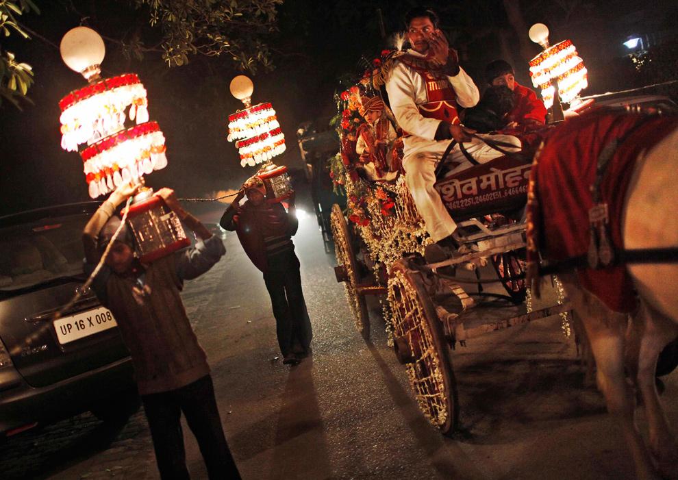 39. Индийские «свадебные» работники несут электрические лампы возле кареты во время свадебной церемонии в Нью-Дели 17 января 2010 года. Лампы соединены вместе и питаются от электричества, источник которого находится в грузовике, который едет следом. (AP Photo/Kevin Frayer)
