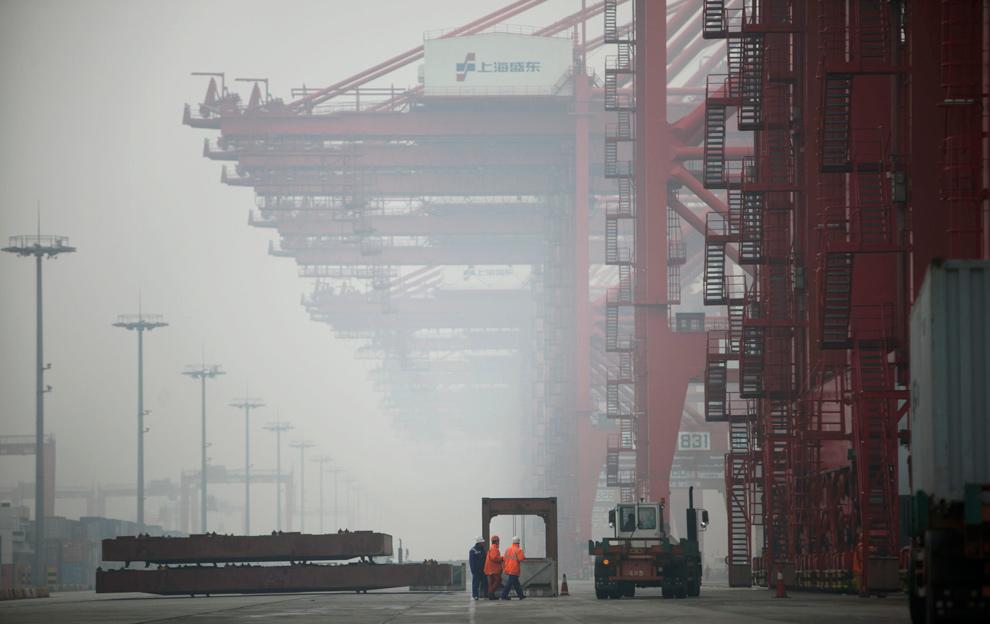 41. Портовые грузчики идут рядом с окутанными туманом козловыми кранами в порту Янгшан в Шанхае 25 января 2010 года. (Qilai Shen/Bloomberg)