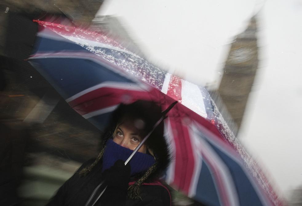 1. Девушка укрывается от сильного снегопада под зонтиком с флагом Великобритании, проходя мимо здания Парламента в Лондоне 6 января. Из-за сильных снегопадов были закрыты аэропорты, главные дороги, а также сотни учебных заведений, кроме того был приостановлены съемки мыльной оперы «Coronation Street». (AP / Alastair Grant)