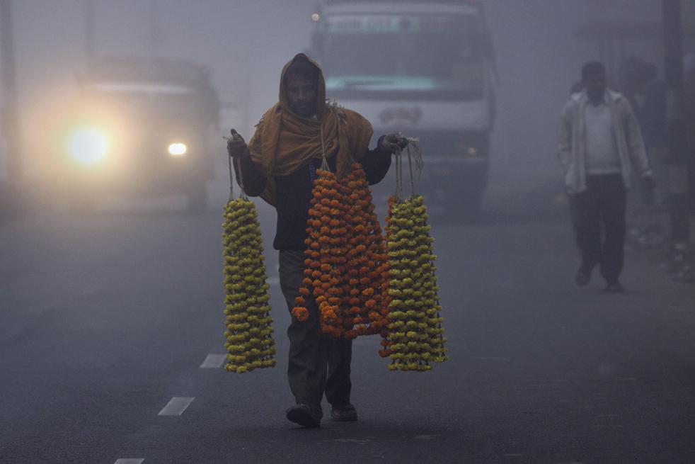 16. Уличный торговец несет гирлянды из бархатцев в густом тумане в Гаухати, Индия 6 января. (AP / Anupam Nath)