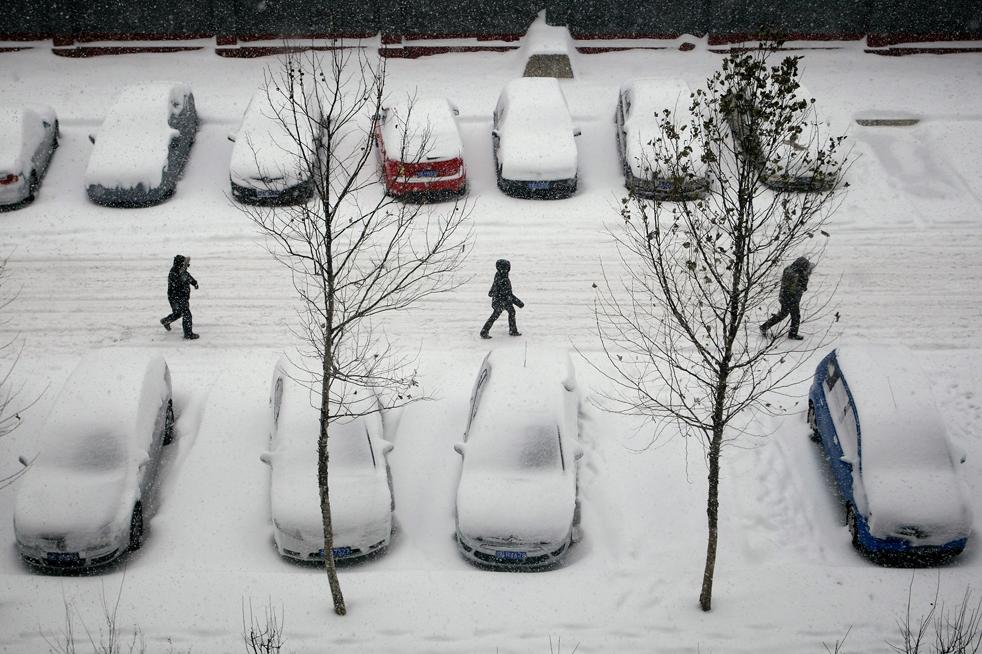 17. Жители Пекина идут по заснеженной улице 3 января. В воскресенье власти Пекина и Тяньцзинь объявили, что в понедельник занятия в начальных и средних школах отменялись из-за снегопада и возникновения пробок. Метеорологи сообщили, что после снегопада в воскресенье температура резко упадет с отметки 7-8 градусов до -16 за три дня, что станет рекордом с 1980 года. (Getty Images / Feng Li)