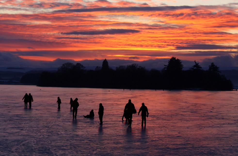 19. Люди идут по замерзшей поверхности озера Ментейт в Шотландии на закате 4 января. (AP / Andrew Milligan)
