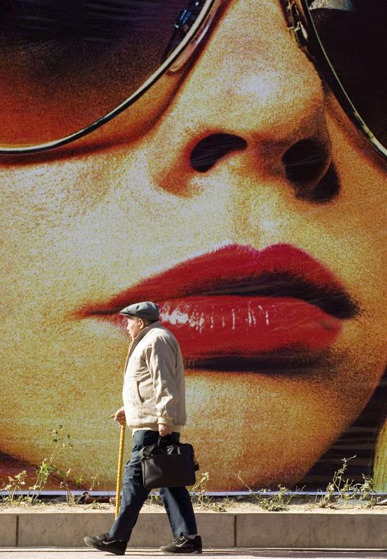 1. Китаец проходит мимо огромного рекламного щита известной косметической фирмы в новом торговом центре в Пекине. Стремясь к глобализации, Китай стремительно начал поглощать западноевропейскую моду, музыку, архитектуру и культуру. (UPI Photo/Stephen Shaver)
