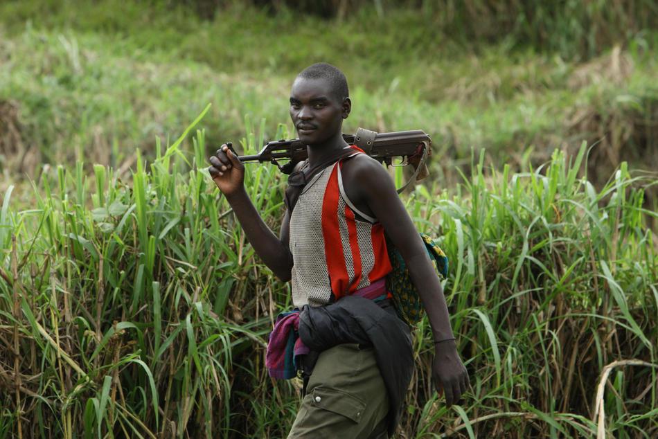 1. Руандийский мятежник Хуту с оружием проходит мимо миротворца ООН в поселке Кимуа в восточном Конго. (AP Photo/Rebecca Blackwell, File)