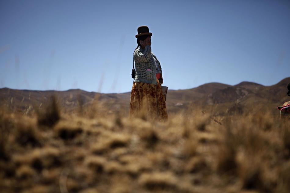 1. Женщина племени аймара разговаривает по мобильному телефону недалеко от деревни Иисус де Мачака, Боливия, 20 августа 2009 года. (AP Photo/Dado Galdieri)