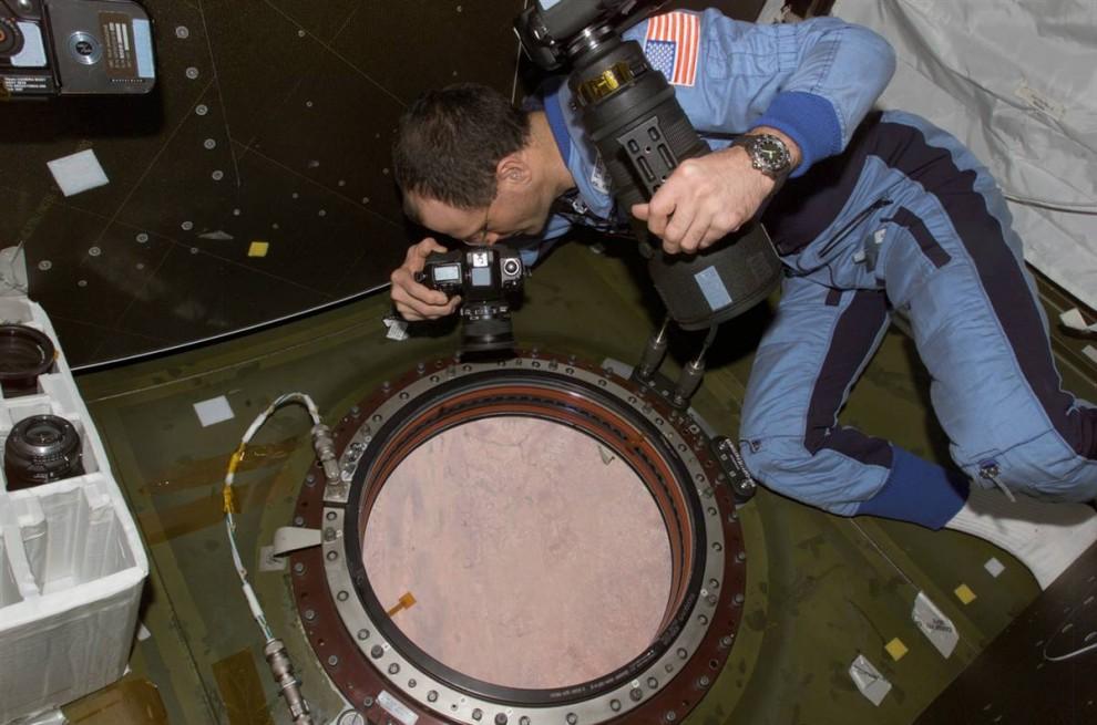 1. Астронавты на борту Международной космической станции используют переносную камеру, чтобы сделать более 450 000 фотографий Земли с расстояния примерно 354 км в небе с ноября 2009 года. Как замечает Синди Эванс из космического центра Джонсона NASA в Хьюстоне, гибкость камеры и возможность менять объективы и изменять интересные ракурсы – вот лишь несколько преимуществ переносной камеры над стационарной. На этом фото Дональд Петти фотографирует Землю из лаборатории «Дестини» на Международной космической станции. (NASA)