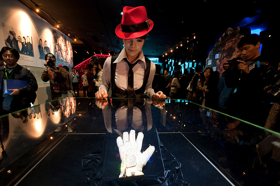 11) Сотрудница Галереи Майкла Джексона выставляет для СМИ знаменитую перчатку Джексона, украшенную драгоценностями. Известность она приобрела в 1983 году, когда в эфире телеканала NBC на шоу «Motown 25» Майкл исполнил песню «Billie Jean». Галерея, расположенная в казино 16 «Ponte 16», открылась в понедельник в Макао. (Victor Fraile/Getty Images)