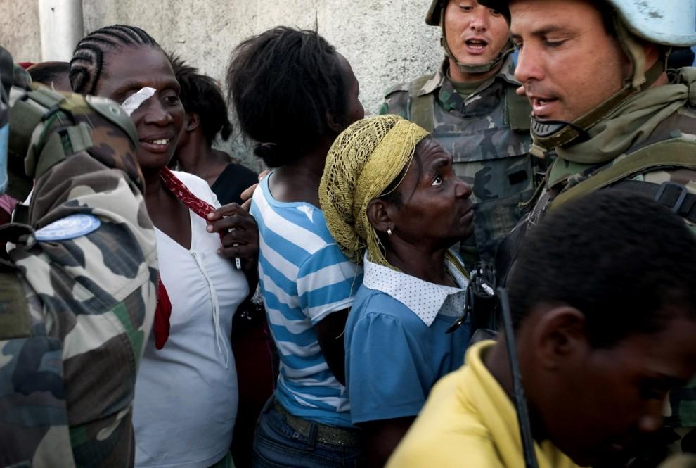 5) Уругвайские миротворцы из Организации Объединенных Наций следят за людьми, стоящими в очереди у пункта распределения продовольствия в Порт-о-Пренс. (Jean-Philippe Ksiazek/Agence France-Presse/Getty Images)