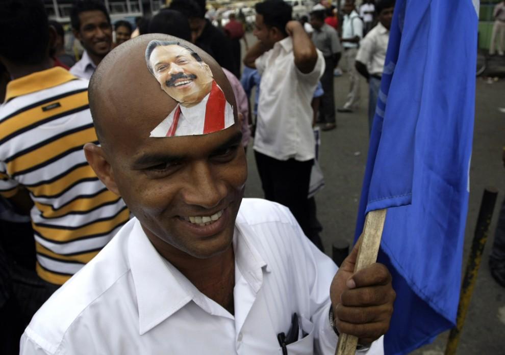 9) Сторонник вновь избранного президента Шри-Ланки Махинда Раджапаксе приклеил его фотографию на лоб. Снимок сделан в столице Шри-Ланки Коломбо. (Eranga Jayawardena/Associated Press)