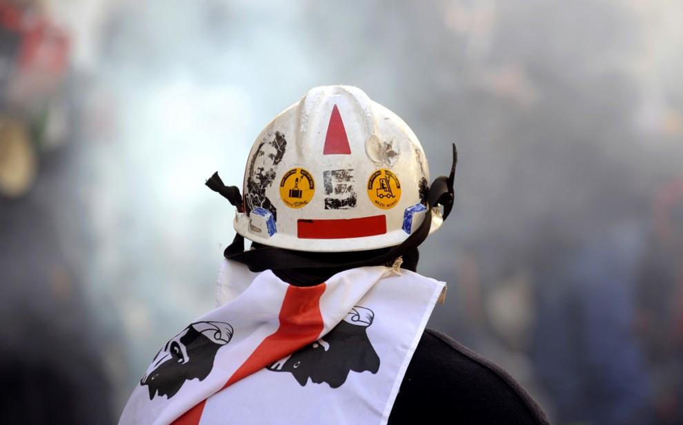 10) Работник компании «Alcoa» наблюдает за взрывами петард во время демонстрации в центре Рима. Сотни рабочих прошли по городу в знак протеста против простоя двух заводов, кроме того заводские работники оккупировали часть взлетной полосе аэропорта в Сардинии. (Alessandro Bianchi/Reuters)