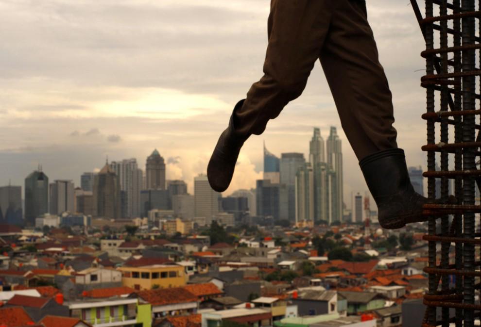 13) Рабочий стоит на стальной балке на  стройке в Джакарте, Индонезия. (Beawiharta/Reuters)