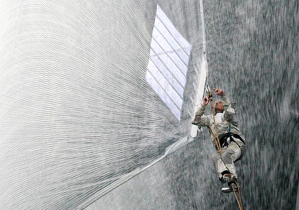 8. Член команды парусной яхты «BMW Oracle» работает с парусами у берегов Валенсии. (Pascal Lauener/Reuters)