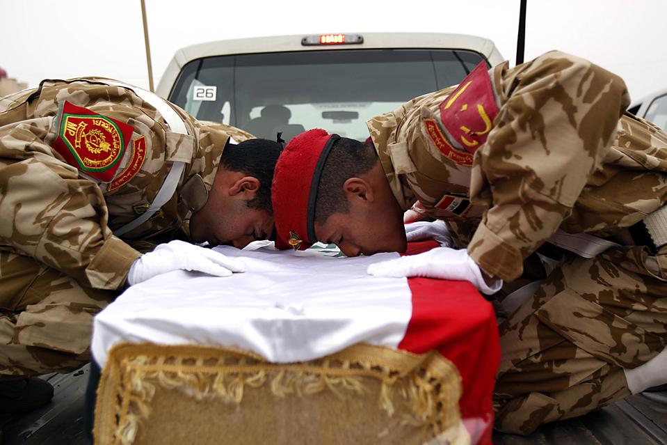 11. Иракские солдаты целуют гроб солдата, чьи останки были получены в четверг у границы недалеко от Басры, Ирак. Останки девяти иракцев, погибших в восьмилетней войне Ирака с Ираном, были возвращены домой. (Nabil al-Jurani/Associated Press)