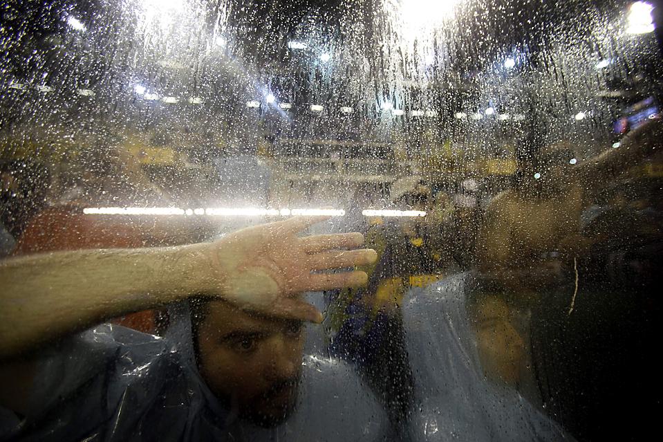 14. Футбольные фанаты ждут под дождем начала матча аргентинской лиги между командами «Boca Juniors» и «Lanus» в Буэнос-Айресе. (Natacha Pisarenko/Associated Press)