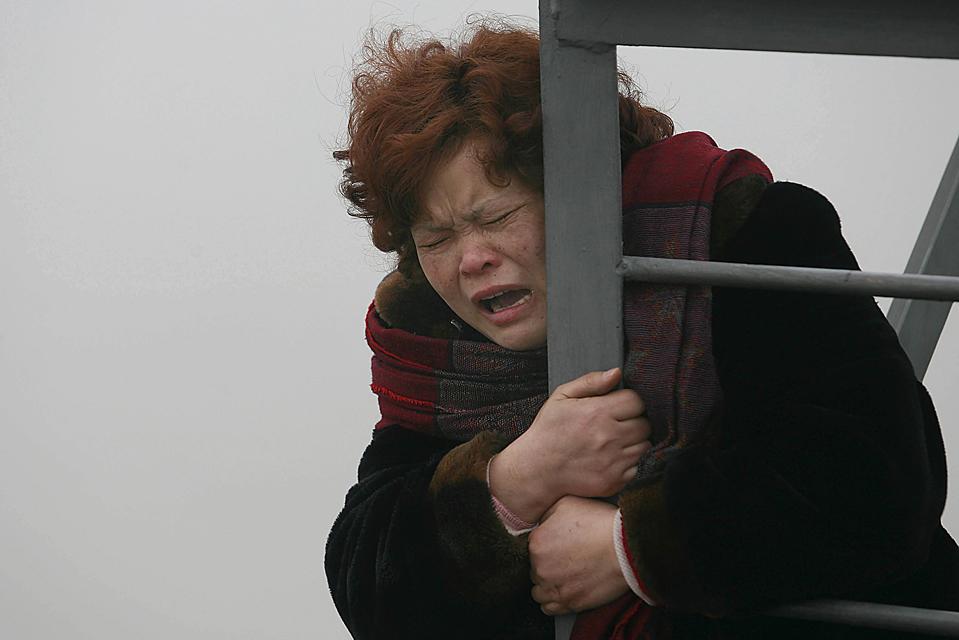6. Женщина во время попытки спрыгнуть с моста в реку Янцзы в Ухане, провинция Хубэй, Китай. Она требовала, чтобы 20 рабочим-мигрантам выплатили полагающиеся им деньги. (Li Jiaqi/European Pressphoto Agency)