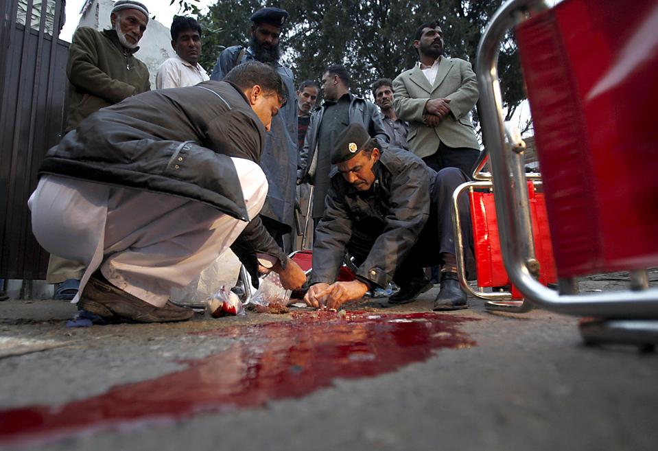 11. Следователи собирают доказательства на месте стрельбы в избирательном участке в Исламабаде. Выборы проходили на место в законодательной палате в Кашмире. (Faisal Mahmood/Reuters)