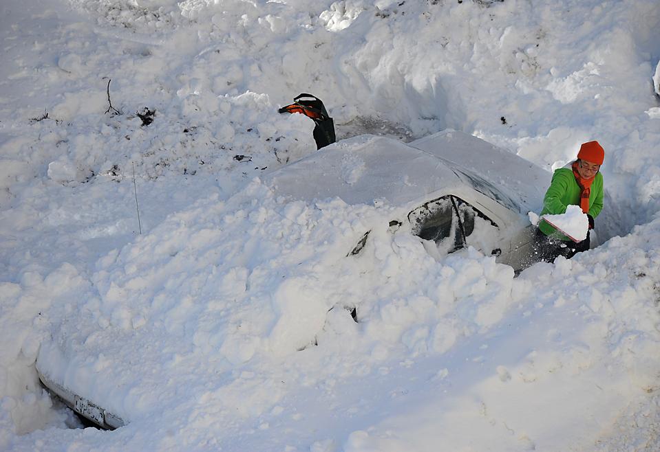 14. Женщина откапывает свою машину в Чеви Сейч, штат Мэриленд. В некоторых среднеатлантических штатах выпало до 90 см снега, а десятки тысяч жителей остались без электричества. (Mandel Ngan/Agence France-Presse/Getty Images)