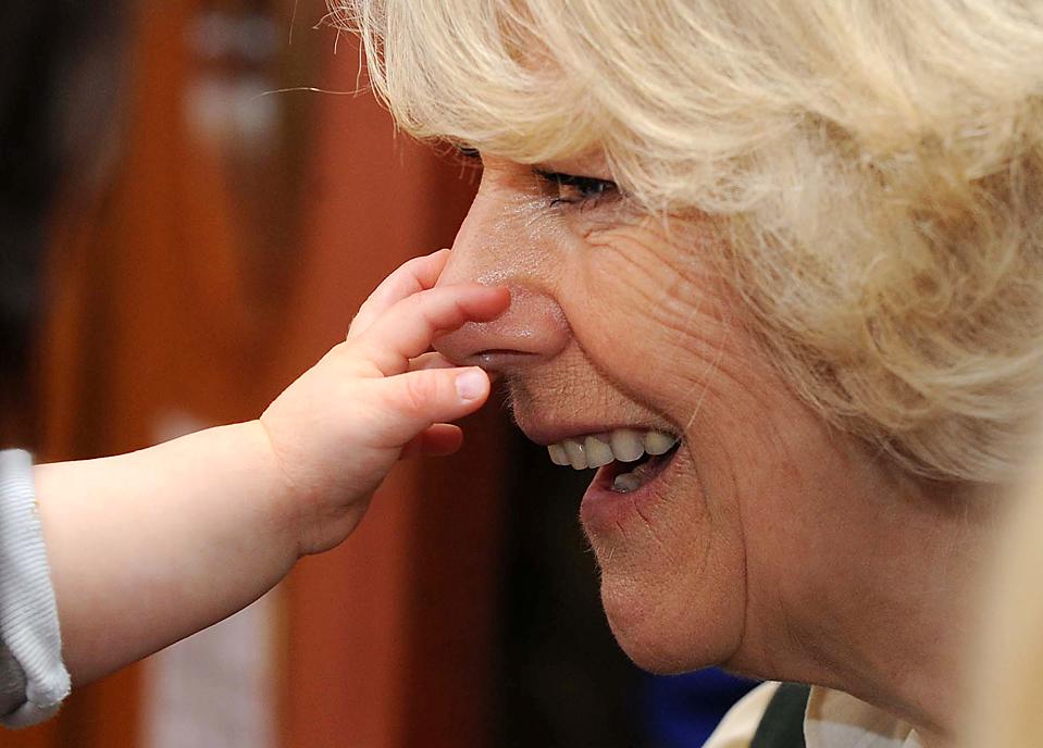 1. 10-месячный Оливер Гидлоу-Джексон прикасается к носу британской герцогини Корнуоллской Камилле, которая приехала в семейный центр на военной базе Булфорд в Солсбери. Дети порадовали герцогиню своими песнями. (David Crump/Daily Mail via Associated Press)