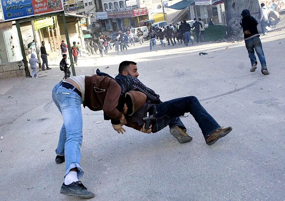 7. Палестинский мятежник (слева) пытается выхватить оружие у израильского полицейского в гражданском во время столкновений в лагере беженцев Шуафат в восточном Иерусалиме. (Bernat Armangue/Associated Press)