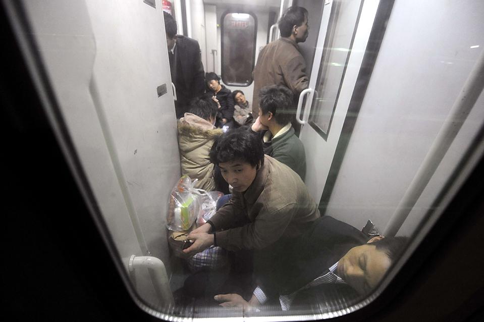 13. Пассажиры отдыхают между вагонами в поезде, покидающем станцию Хэфэй в провинции Аньхой, Китай. В поездах нет свободных день, так как люди разъезжаются по домам, чтобы отпраздновать китайский новый год. (Reuters)