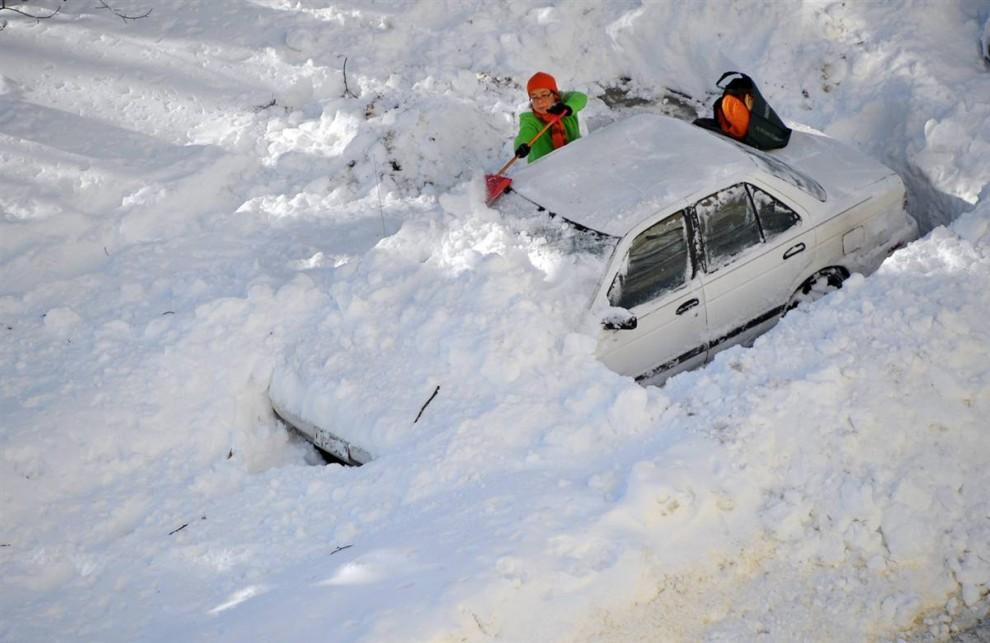2. Женщина расчищает снег с автомобиля после сильного снегопада в Чеви Чейс, штат Мэриленд. (Mandel Ngan / AFP - Getty Images)