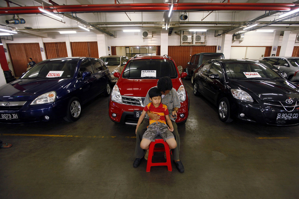 1. Торговец подержанными автомобилями ждет с сыном клиентов в своем салоне в Джакарте. (Beawiharta/Reuters)