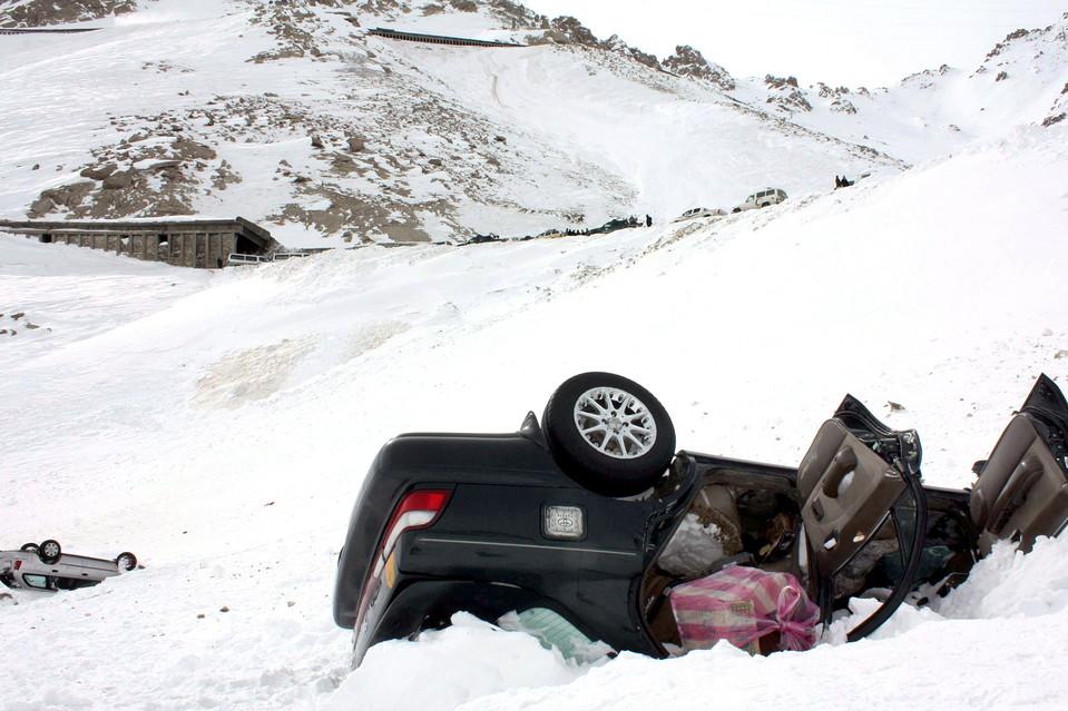 2. Перевернутые автомобили лежат в снегу вдоль проезда Саланг в Афганистане. Количество погибших в результате схода лавины, накрывшей главную дорогу, достигло уже 157 человек. Солдаты и полиция продолжают откапывать людей из-под завалов. (S. Sabawoon/European Pressphoto Agency)