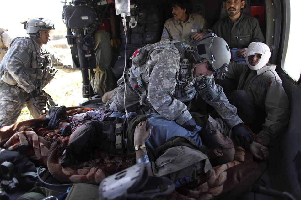 8. Военный медик сержант Браен Айкельберг трет грудь офицеру Национальной афганской полиции после того, как он получил серьезное ранение в результате взрыва в провинции Гильменд. (Brennan Linsley/Associated Press)