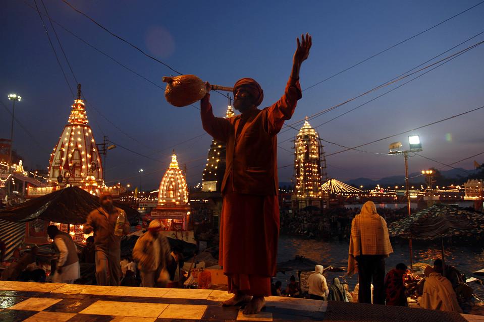 13. Индус молится, пока другие окунаются в священные воды реки Ганг во время фестиваля Кумбха Мела в Харидваре, Индия. (Rajesh Kumar Singh/Associated Press)