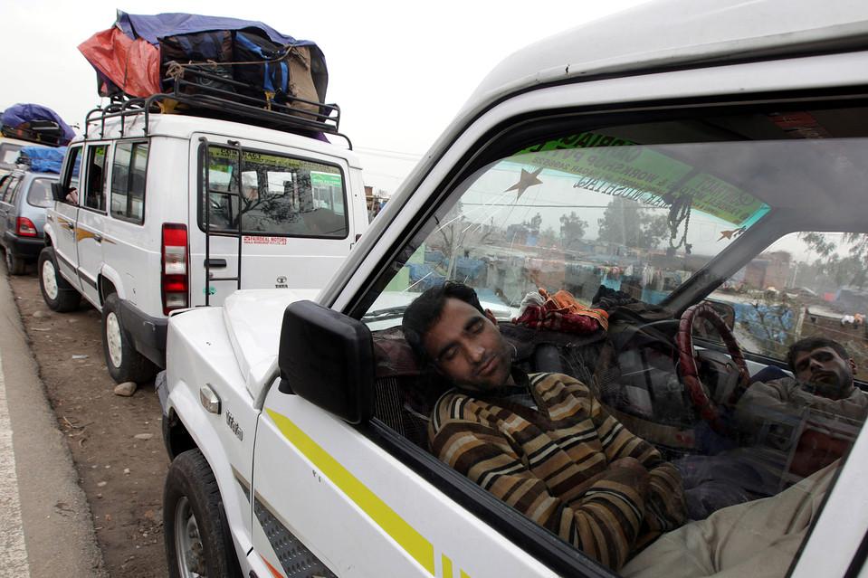 14. Застрявшие в пробке пассажиры спят в своих автомобилях на дороге в Джамму, Индия. К долине Кашмир по-прежнему не проехать из-за сильных снегопадов и оползней. (Jaipal Singh/European Pressphoto Agency)