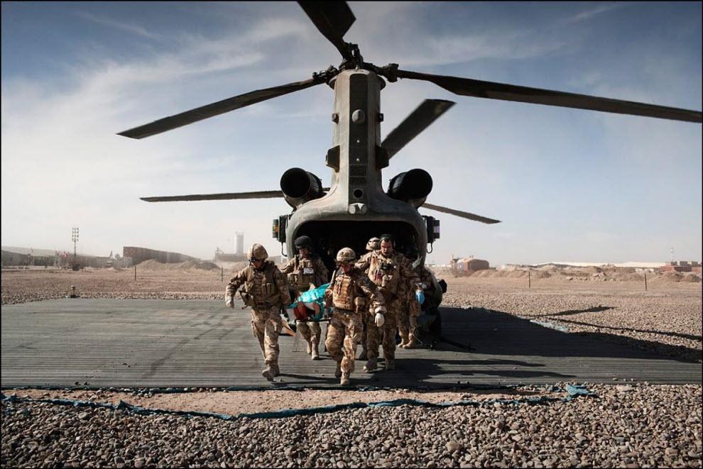 02) Команда MERT несет носилки с раненым британским солдатом с борта вертолета в госпиталь Кэмп Бастион.