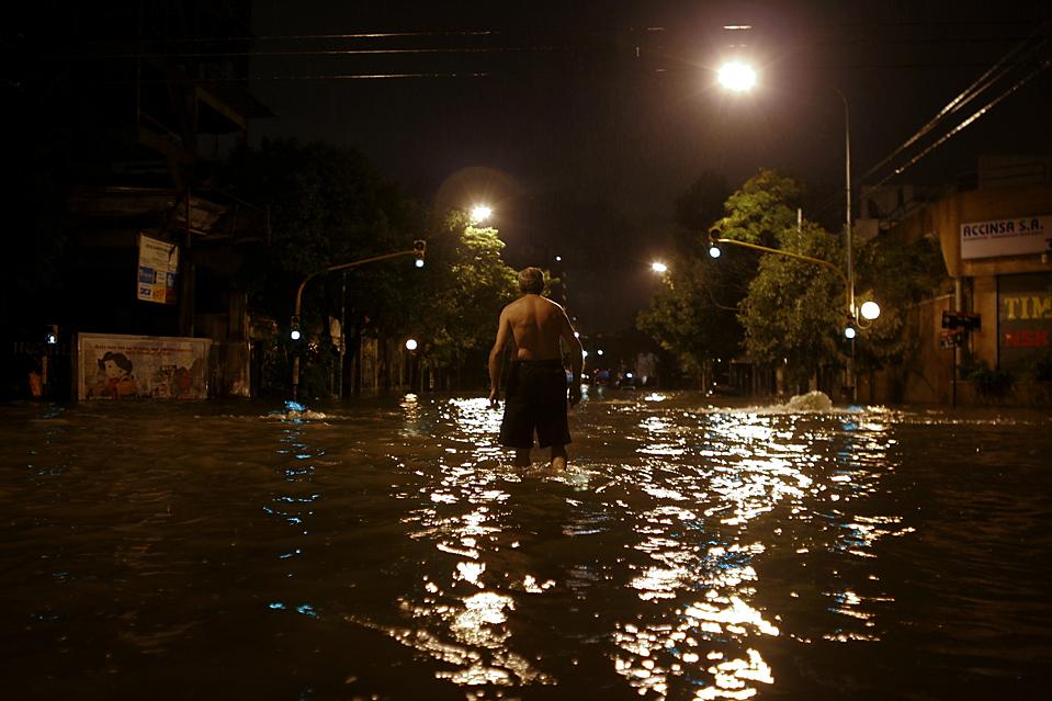 6. Мужчина идет по затопленной улице во время шторма в Буэнос-Айресе. (Natacha Pisarenko/Associated Press)