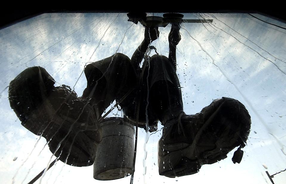 3. Рабочий чистит окно офисного здания в Хайдарабаде. (Krishnendu Halder/Reuters)