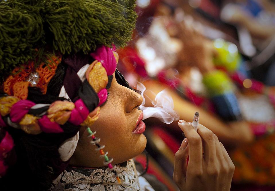 9. Модель Амна Ильяс курит перед выходом на подиум в наряде от Ники Нина во время недели моды в Лахоре, Пакистан. (Adrees Latif/Reuters)