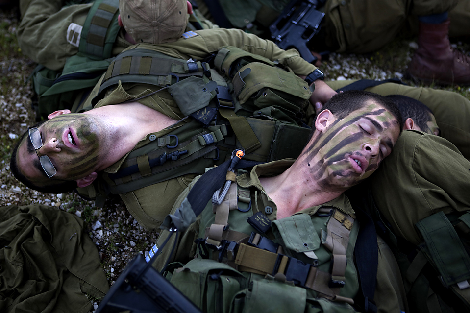 11. Солдаты израильской армии отдыхают недалеко от долины Иордан после похода всю ночь. Лидер движения «Хезболлах» Хасан Насралла поклялся натравить всю мощь своих боевых сил на израильские инфраструктуры. (Menahem Kahana/Agence France-Presse/Getty Images)