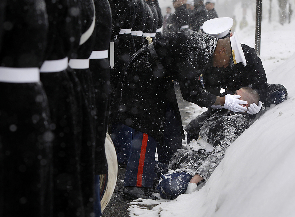 12. Товарищи помогают солдату почетного караула, упавшему в обморок во время похорон конгрессмена Джона Мурта, в Джонстауне, штат Пенсильвания. Мурта скончался 8 февраля в возрасте 77 лет в результате осложнений после операции на желчный пузырь. (Carolyn Kaster/Associated Press)