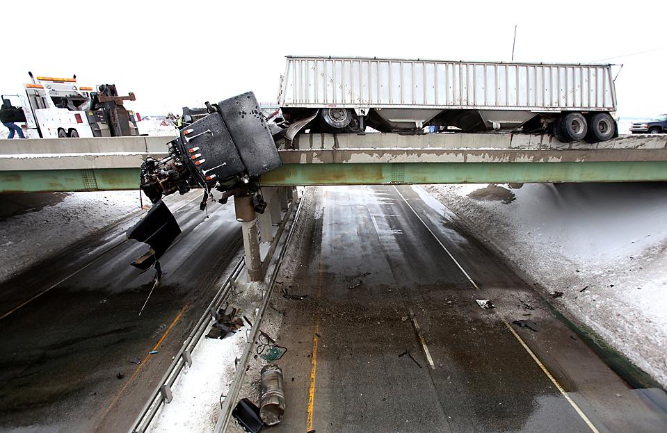 7. Часть грузовика, столкнувшегося с автомобилем, свисает с моста на шоссе 67 недалеко от Мюнци, штат Индиана. Водитель автомобиля серьезно пострадал, в то время как водитель грузовика успел выпрыгнуть из машины. (Chris Bergin/The Star Press via Associated Press)