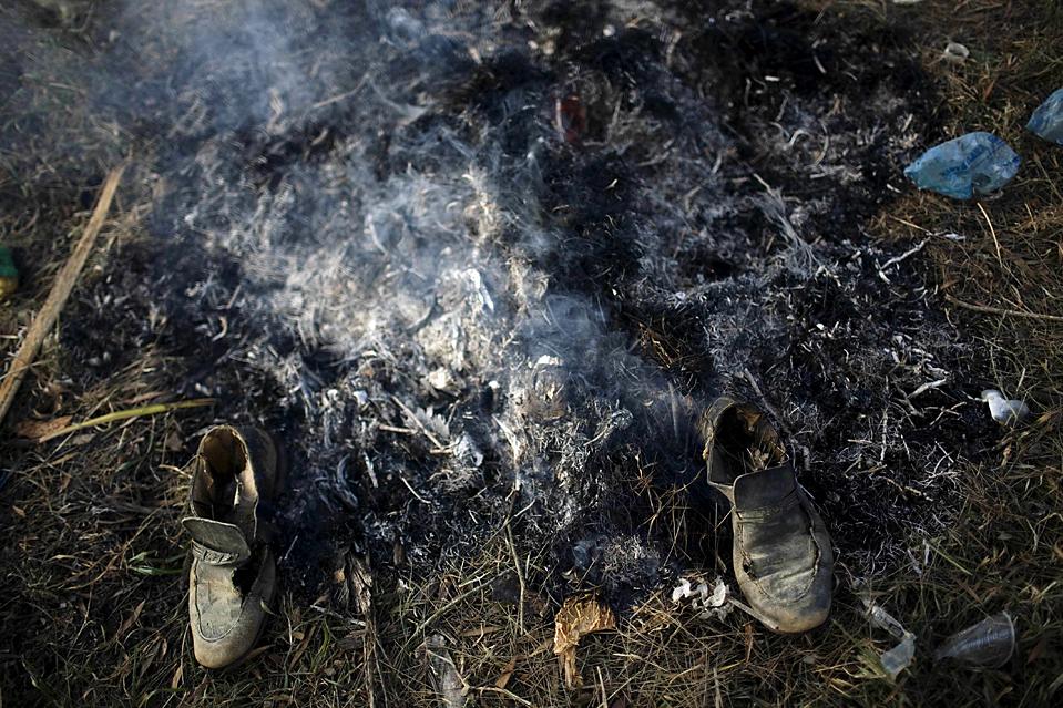 12. Сожженная обувь стоит на месте пожара в Гватемале на месте массового захоронения на одном из крупнейших кладбищ города. Судебные медики надеются собрать данные, которые помогут идентифицировать тела погибших в Гражданской войне. (Rodrigo Abd/Associated Press)
