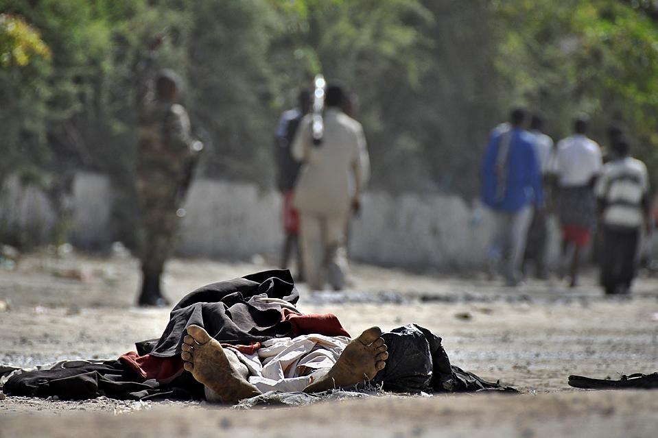 13. Тело одного из двух мужчин, погибших в результате взрыва, который они же сами и пытались устроить на дороге, в Могадишу. (Mustafa Abdi/Agence France-Presse/Getty Images)