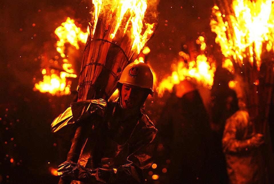 """4) Участники карнавала несут горящие деревянные палки во время традиционного огненного парада """"Chienbaese"""" в городе Листаль, Швейцария. (Michael Buholzer/Reuters)"""