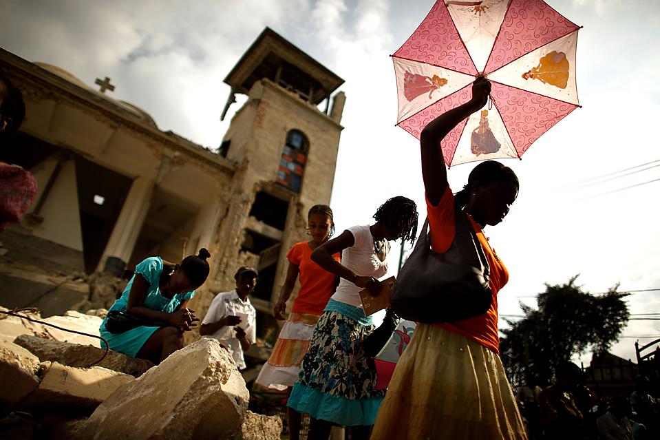 5) Молодые женщины перебираются через камни после посещения мессы в разрушенном землетрясением католическом соборе столицы Гаити Порт-о-Пренс. (Chip Somodevilla/Getty Images)