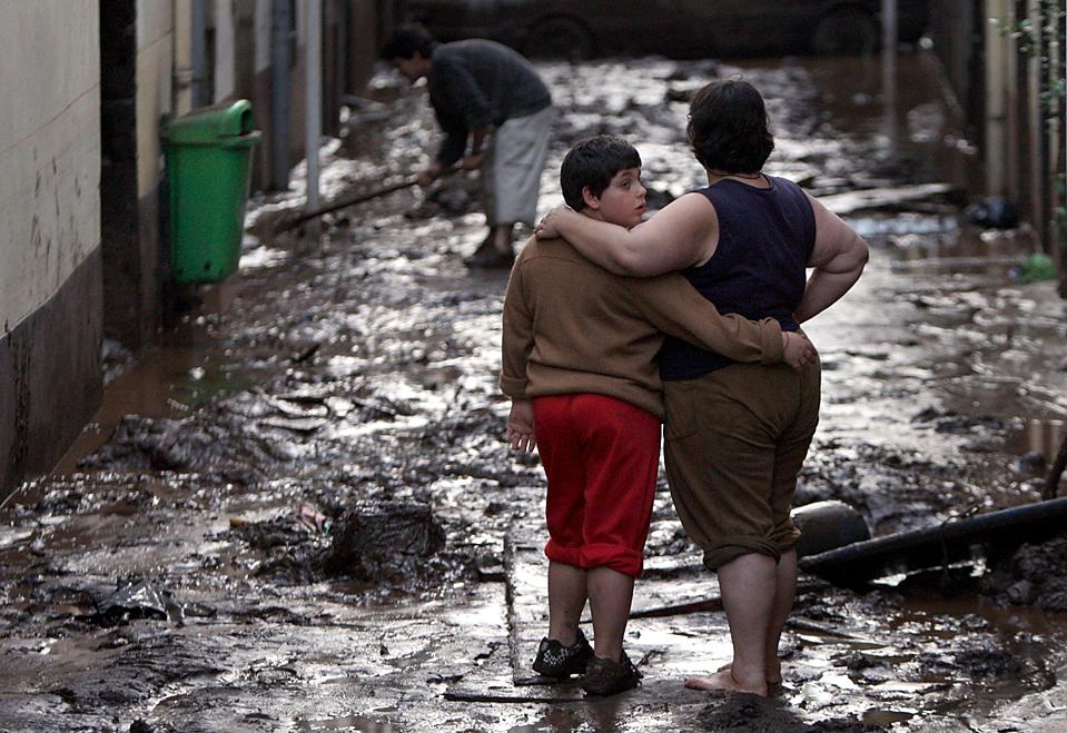 6) Женщина и ее сын стоят на покрытой грязью улице после сильного наводнения в городе Фуншал, на португальском острове Мадейра. Из-за оползней, вызванных наводнением погибли, по меньшей мере, 42 человека. (Manuel de Almeida/European Pressphoto Agency)