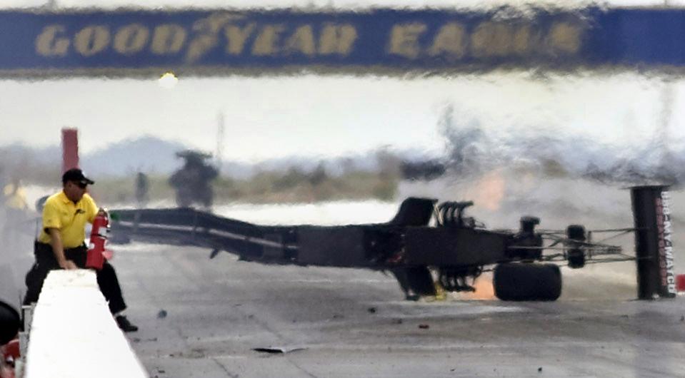 14) Работник гоночного трека перелезает через барьер с огнетушителем, чтобы помочь пилоту Антронону Брауну после того как разбился его болид-драгстер Matco Tools/U.S. Army. Инцидент произошел во время гонок NHRA в Аризоне. Пилот не пострадал, однако в результате удара отлетевшей шиной болида скончалась женщина. (Crystal Ochoa/The Arizona Republic via Associated Press)