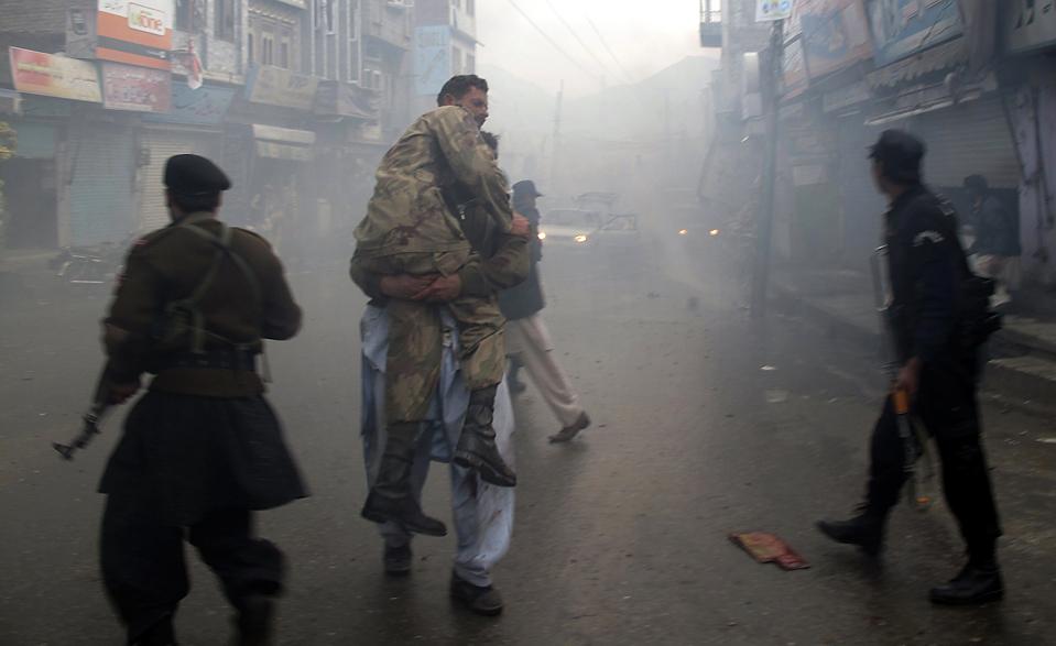15) Владелец магазина несет раненого солдата с места взрыва, произошедшего в пакистанском городе Мингаора. Из-за взрыва на оживленном рынке, причиной которого стал террорист-смертник, погибли по меньшей мере восемь человек и десятки получили ранения. (Hazrat Ali Bacha/Reuters)