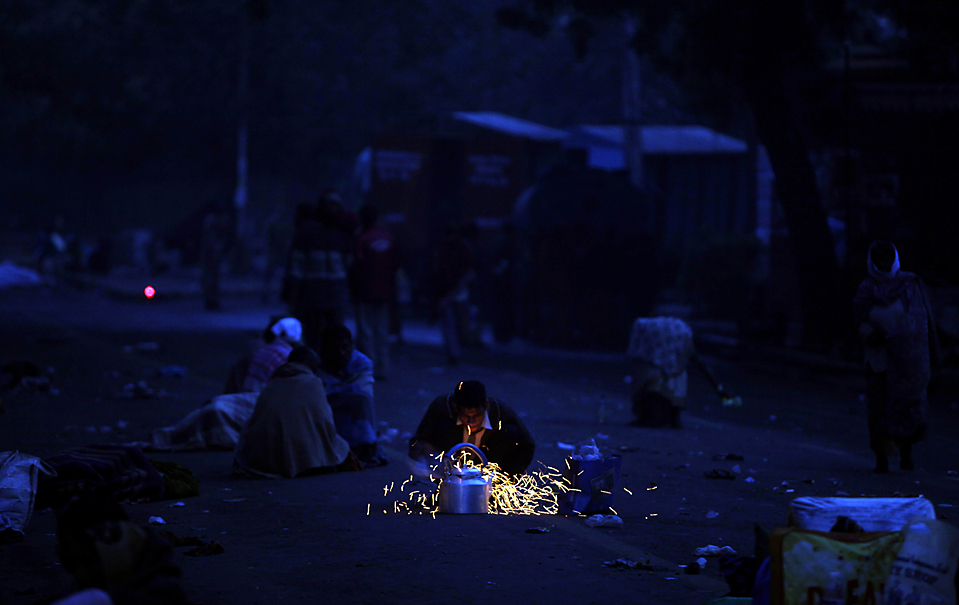 9. Уличный торговец чаем греет чайник, пока демонстранты спят на дороге недалеко от здания индийского парламента в Нью-Дели. Местные жители собрались в столице с протестами во время заседания парламента по вопросам бюджета. (Mustafa Quraishi/Associated Press)